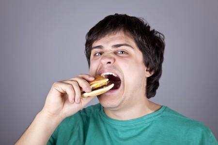 Cute boy eating hamburger. Studio shot.  photo