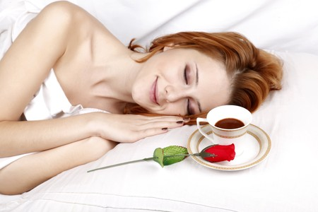 Red rose and cup of coffee near pretty red-haired sleeping woman in white in the bed. photo