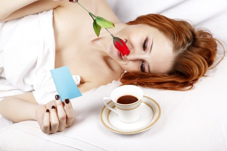 Pretty red-haired sleeping woman in white reading note and lying near cup of coffee and red rose in the bed.  photo