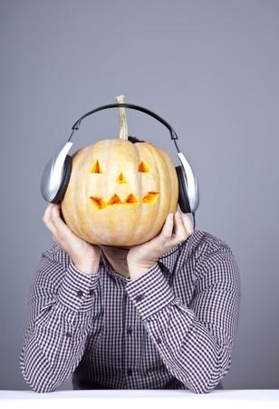 Funny men with pumpkin and headphone. Studio shot. photo