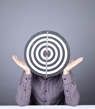 Boy with dartboard in place of head. Studio shot.  photo