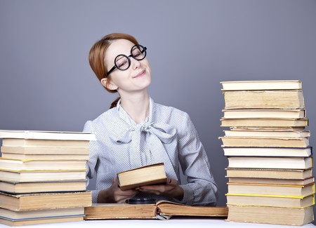 exam preparation: The young teacher in glasses with books. Studio shot.