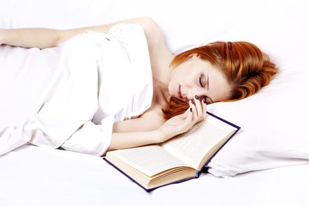luxuriate: Pretty red-haired woman in white nightie lying in the bed near book. Studio shot.