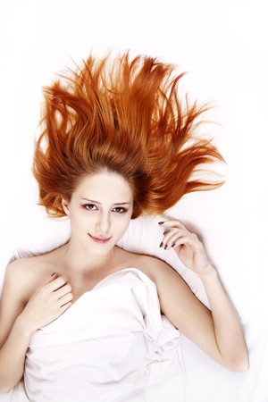 nightie: Pretty red-haired woman in white nightie lying in the bed. Photo in vogue style.
