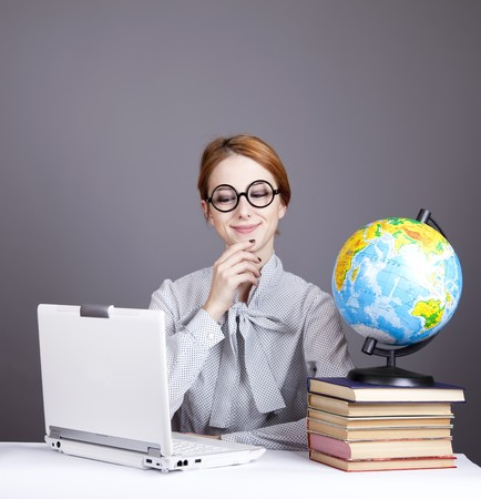 exam preparation: The young teacher in glasses with books, globe and notebook. Studio shot.