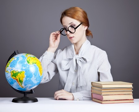 The young teacher in glasses with books and globe. Studio shot.  photo