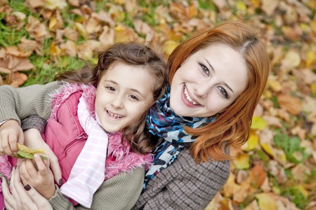 Two sisters sitting on the leafs in the park. Outdoor shot. photo