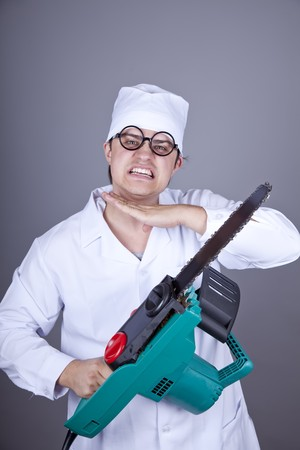 nuthouse: Crazy doctor with portable saw. Studio shot. Stock Photo