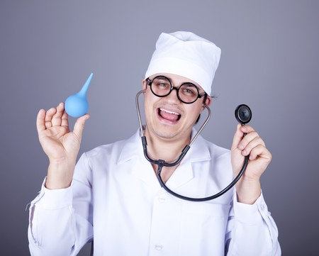 Crazy doctor with a stethoscope and enema. Studio shot. photo