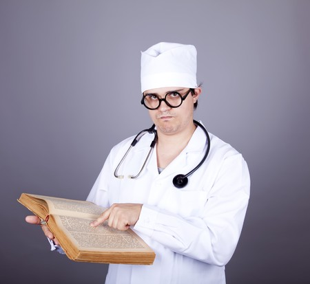 Young doctor with book. Studio shot. Stock Photo - 8134250