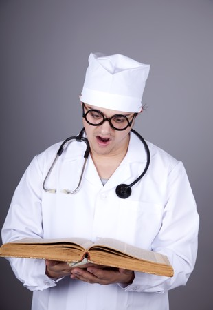 Young doctor with book. Studio shot. photo