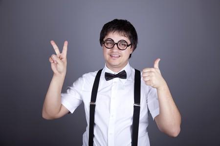 suspender: Portrait of funny fashion men in suspender with bow tie and glasses show OK symbols. Studio shot.