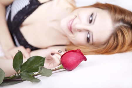 luxuriate: Beautiful red-haired girl with rose in the bedroom. Indoor shot.