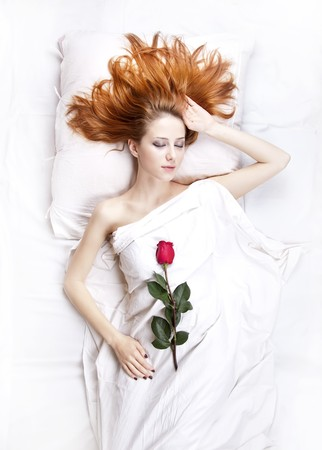 Fashion red-haired girl with rose in the bedroom. Studio shot from top. photo