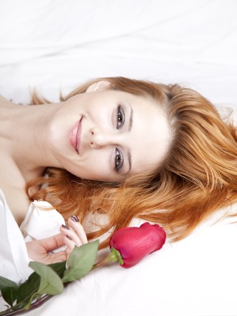 Beautiful red-haired girl with rose in the bed. photo