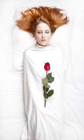 luxuriate: Fashion red-haired girl with rose in the bedroom. Studio shot from top.