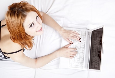 luxuriate: Beautiful red-haired girl with notebook in the bed. Studio shot.