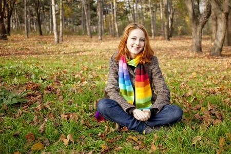 Portrait of red-haired girl in the autumn park. Outdoor shot. photo