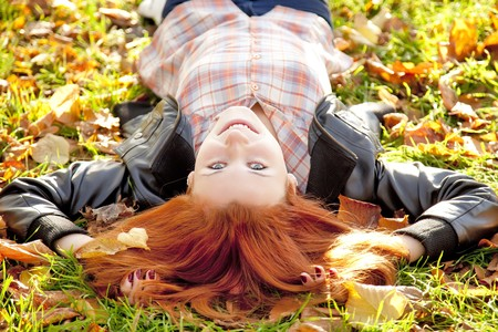 Happy red-haired girl at the park in autumn. Outdoor shot. photo