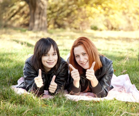 Two beautiful girlfriends at the autumn park near tree. Outdoor shot. photo