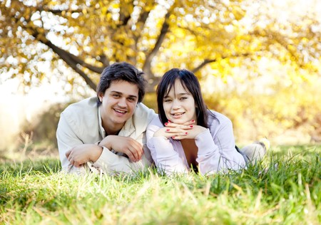 Couple lie at green grass in the park. Outdoor shot. photo