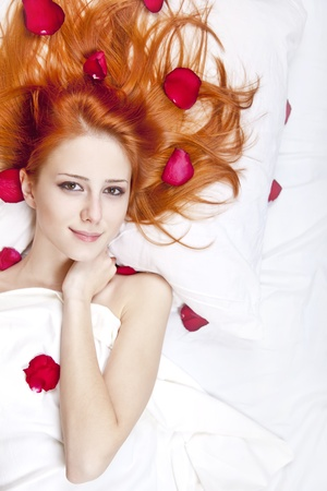 luxuriate: Beautiful red-haired girl in bed with rose petal. Studio shot.