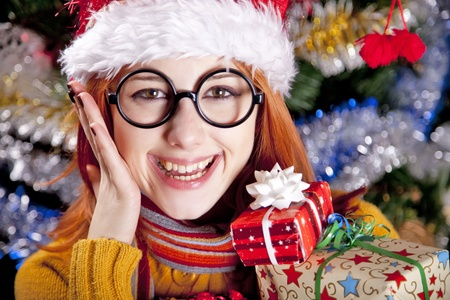 Funny girl in christmas cap with gift boxes and tree at background. photo