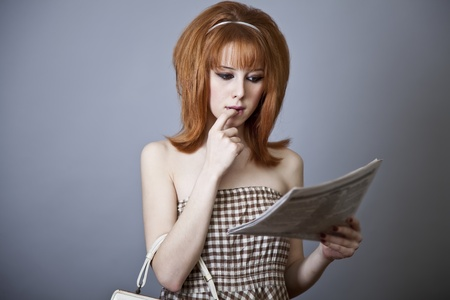 Portrait of red-haired girl with newspaper. 60s style. photo