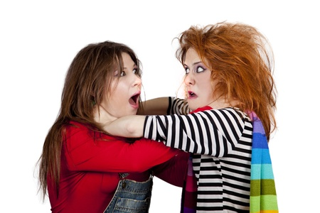 to strangle: Two funny angry girls. One of them strangle to other. Studio shot.