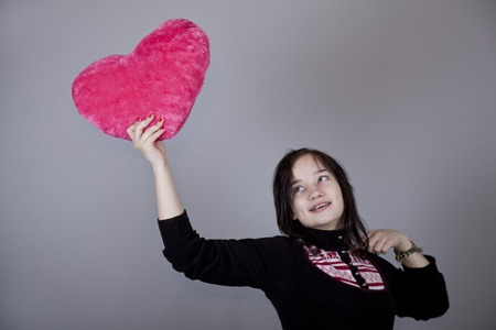 gril: Funny gril with toy heart. Studio shot. Stock Photo