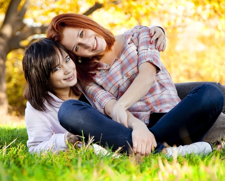 Two beautiful teen girl at green grass in the park. photo