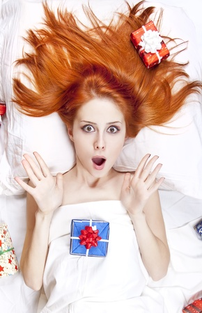 luxuriate: Surprised red-haired girl in bed with Christmas gifts. Studio shot. Stock Photo