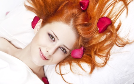 Beautiful red-haired girl in bed with rose petal. Studio shot. photo