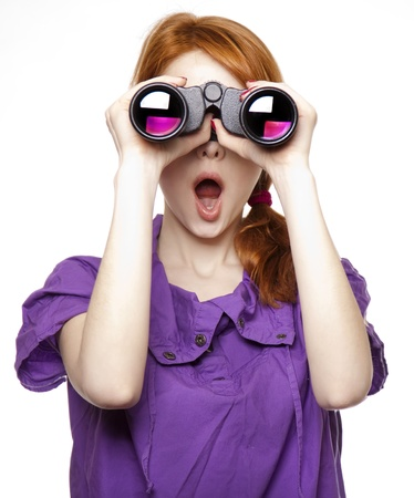 surprised face: Teen red-haired girl with binoculars isolated on white background