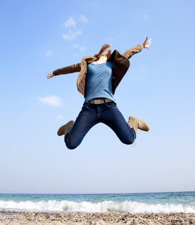 Young beautiful girl jumping at the beach. photo