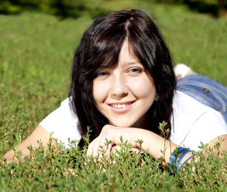 Portrait of beautiful brunette girl with blue eyes on green grass in the park. photo
