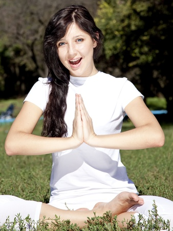 Beautiful young brunet yoga girl on green grass in park. Stock Photo - 9125440
