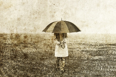Girl with umbrella staying on field.  photo
