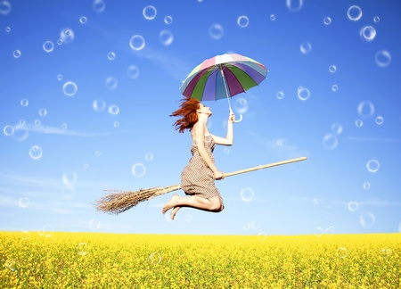 brooms: Red-haired girl fly with umbrella over rape field and bubbles around.