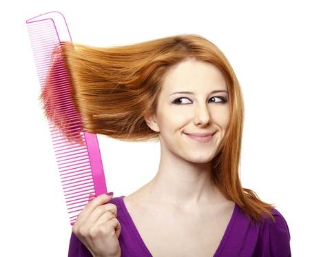 Divertente ragazza dai capelli rossi con grosso pettine.
