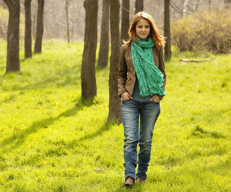 Beautiful red-haired girl walking at green grass at park.  photo
