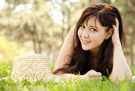 Beautiful brunette girl with hat at the park. photo