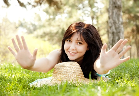 Beautiful brunette girl with hat at the park show hir palms. photo