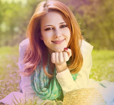 pelirrojas: Chica pelirroja en c�sped en el parque. Foto en estilo multicolor.