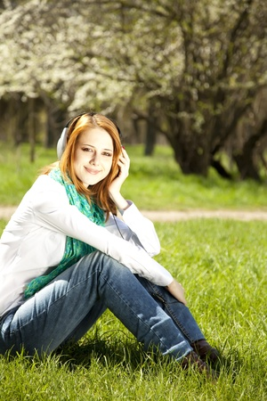 Redhead girl with headphone in the park.  photo