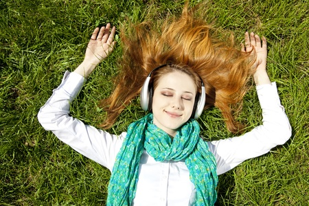 Redhead girl with headphone lies in the park. photo