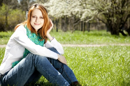 Redhead girl with headphone in the park.