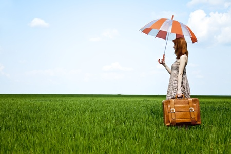 enchantress: Redhead enchantress with umbrella and suitcase at spring wheat field. Stock Photo