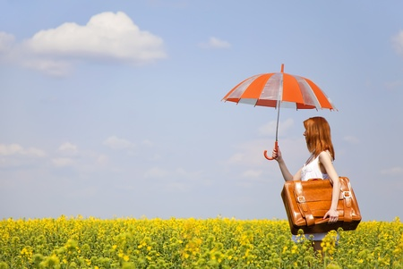 adult rape: Redhead enchantress with umbrella and suitcase at spring rapeseed field.
