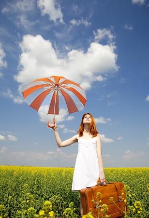 femme avec valise: Enchanteresse Redhead avec parasol et valise au champ de colza de printemps.